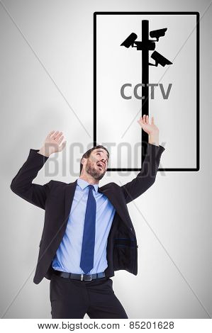 Shocked businessman standing and pushing up against cctv