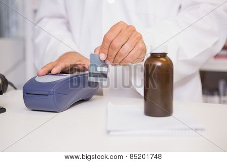 Pharmacist using keypad with credit card in the pharmacy