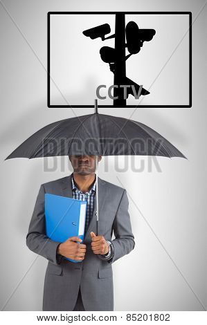 Businessman standing under umbrella against cctv