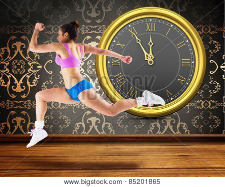 Fit brunette running and jumping against room with wallpaper
