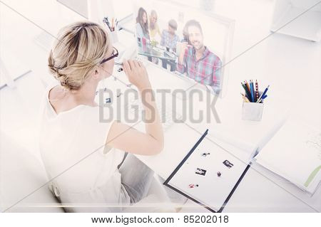 Composite image of female photo editor working on computer