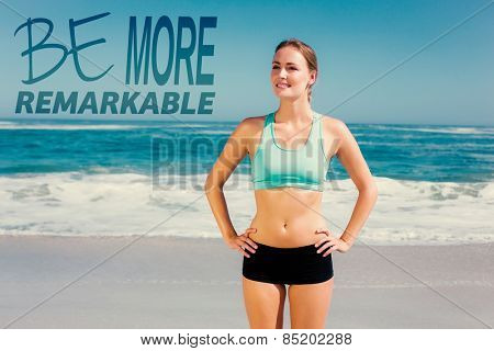 Fit woman standing on the beach with hands on hips against be more remarkable