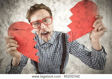 Geeky hipster holding a broken heart against grey background