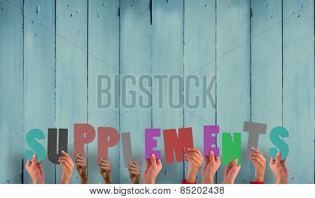 Hands holding up supplements against wooden planks