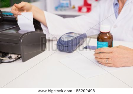 Pharmacist holding jar of medicine and receipt in the pharmacy