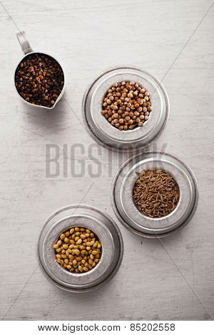 coriander seeds black and white, cardamom and cumin in   in vintage  old dishes,  tin metal background, closeup
