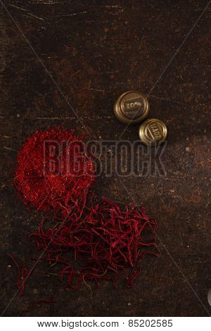 saffron spice in pile threads and powder on old metal background, closeup
