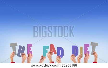 Hands holding up the fad diet against bright blue sky