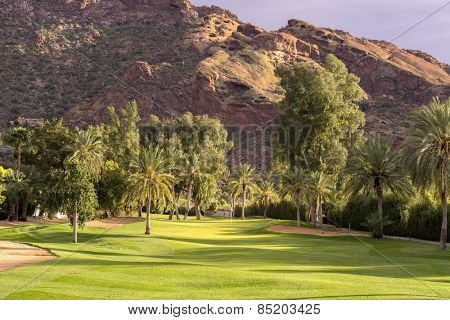 Golf course fairway bathed in beautiful golden hour light with Camelback Mountain in background, Phoenix,Az,USA