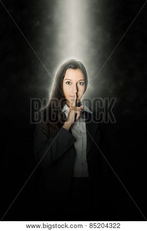 Pretty young businesswoman making a shushing gesture holding her finger to her lips as she asks you to keep a secret and remain quiet while standing in a single beam of light in the darkness
