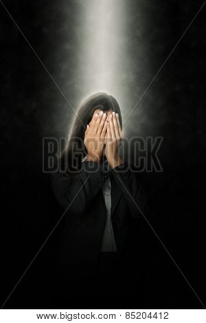Close up Glowing Head of an Office Woman Covering her Face with her Both Hands on an Abstract Black Background.