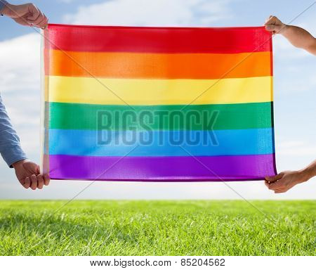 people, homosexuality, same-sex, gay and love concept - close up of happy male gay couple hugging and holding rainbow flag over blue sky and grass background