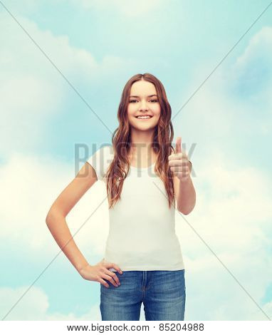 t-shirt design concept - smiling teenager in blank white t-shirt showing thumbs up