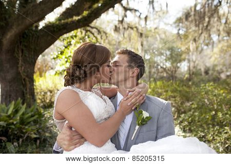 Young newly married couple kissing, groom carrying bride in the garden
