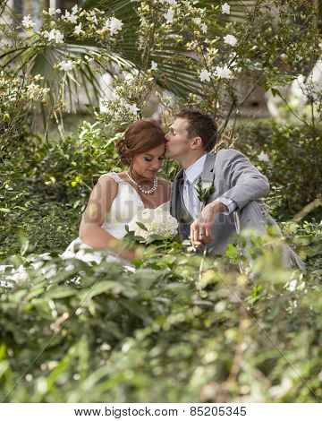 Beautiful married couple on wedding day in garden, groom kissing bride