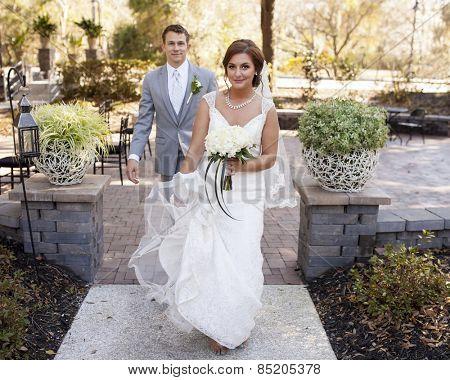 Bride and groom walking in garden area