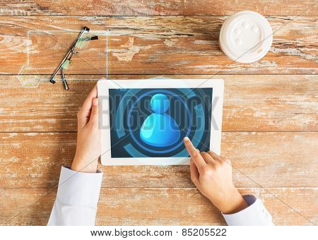 business, people, communication and technology concept - close up of hands pointing finger to tablet pc computer screen with user icon, coffee cup and eyeglasses on table