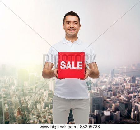 shopping, consumerism, discount and people concept - smiling man with red sale sigh up over city background