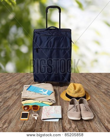 summer vacation, tourism and objects concept - travel bag, map, air ticket and clothes with personal stuff over wooden floor and nature background