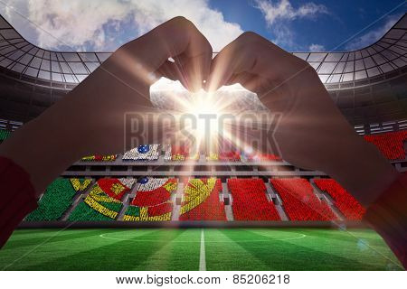 Woman making heart shape with hands against stadium full of portugal football fans