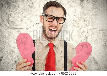 Geeky hipster crying and holding broken heart card against grey background
