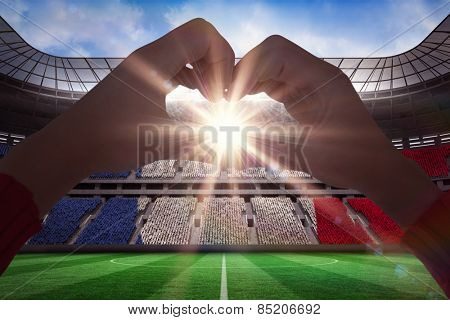 Woman making heart shape with hands against stadium full of france football fans