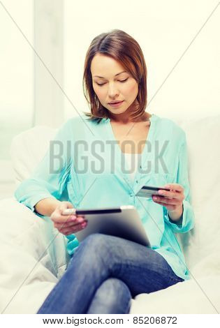 home, technology, online shopping and internet concept - smiling woman sitting on the couch with tablet pc at home