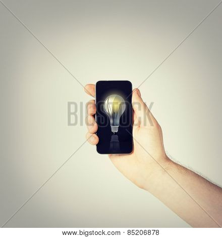 environment, ecology and technology - man hand holding smartphone with light bulb sign