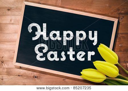 Yellow tulips against small blackboard on wooden floor