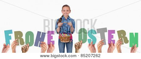 Hands holding up frohe ostern against portrait of a girl holding a basket full of easter eggs