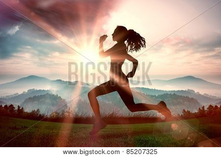 Full length of healthy woman jogging against sun shining over mountains
