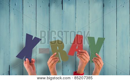 Hands holding up xray against wooden planks