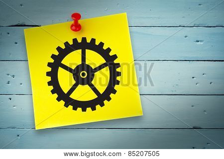 Cog graphic against pinned adhesive note