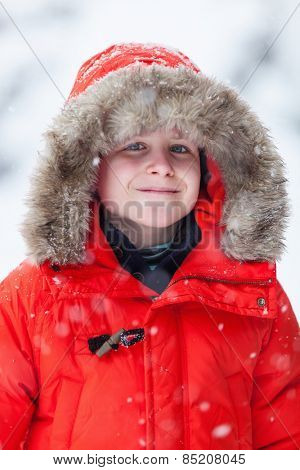 Cute boy in a red parka down jacket outdoors on beautiful winter snow day