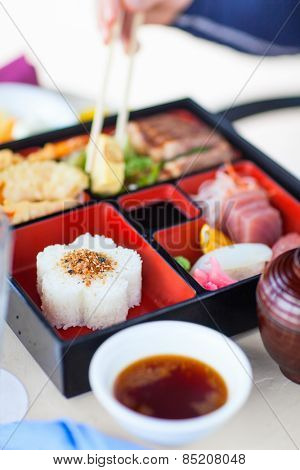 Delicious Japanese lunch bento box with rice, fish sashimi, omelet, meat and vegetables
