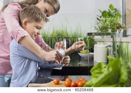 Mother assisting son in folding sleeves while washing hands in kitchen