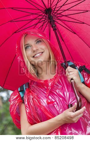 Smiling female hiker in red raincoat holding umbrella