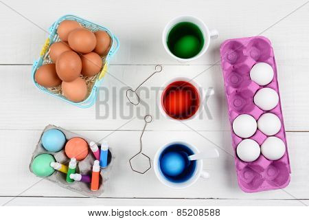 High angle still life of dying eggs for Easter. Three cups with dye, a basket of brown eggs and cartons of undyed and dyed eggs on a rustic white wood kitchen table.