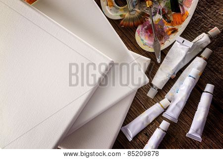 Pure blank canvas and professional acrylics paints in tubes, palette with artistic putty knife and brushes