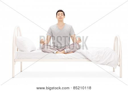 Calm guy meditating seated on bed isolated on white background