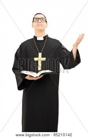 Vertical shot of a young male priest praying to god and holding a bible isolated on white background