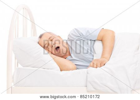 Studio shot of a mature man sleeping in bed isolated on white background