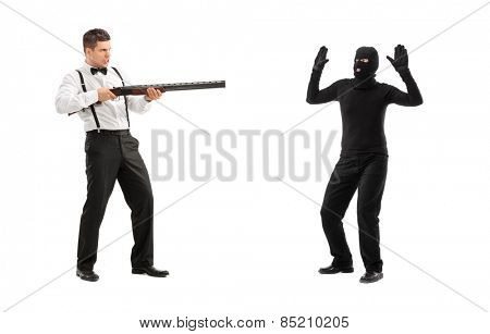 Angry man threatening a burglar with rifle isolated on white background