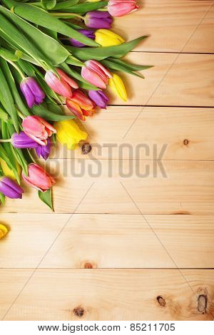 Spring Flowers bunch at wood floor texture. Beautiful Tulips bouquet gift. Easter or Mother's Day  background. Springtime or summertime. Invitation card design with space for your text
