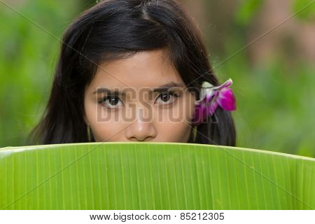 Portrait of a young Vietnamese woman peeking over the top of a banana tree leaf at the camera