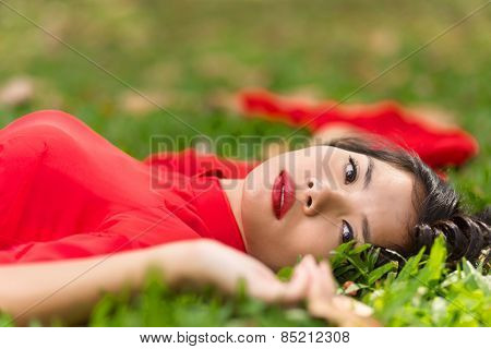 Happy Young Pretty Asian Woman in Red and White Dress Lying Down on Grassland
