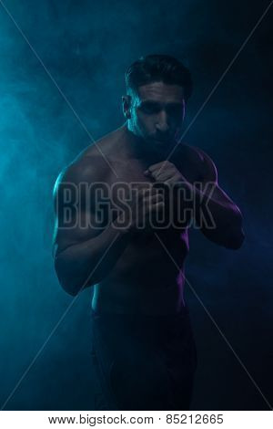 Portrait of a Silhouette Topless Athletic Man in a Fighting Pose Looking at the Camera on a Hazy Blue Green Background