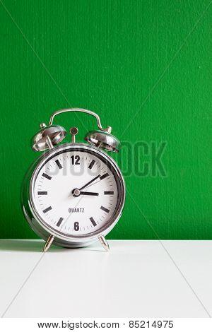 alarm clock near green wall