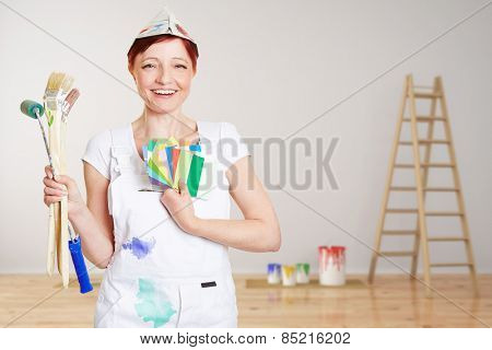 Happy woman with brushes and different colors painting wall in a room (3D Rendering of background)