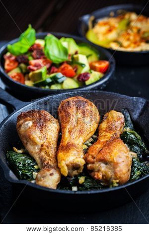 Crispy chicken legs on spinach with avocado salad